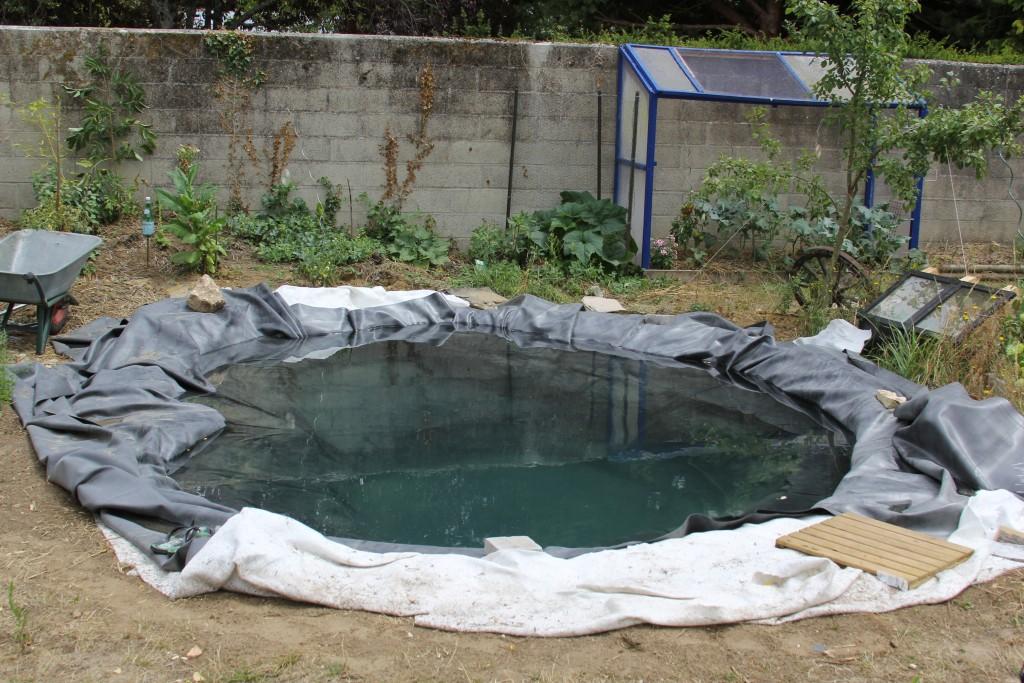 On pose la bâche EPDM du bassin de jardin extérieur